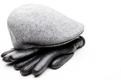 Tweed grey cap black leather gloves white background. Studio quality Royalty Free Stock Photo