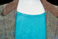 Tweed jacket. Close up of part of a tweed jacket over a blue jumper Stock Photography
