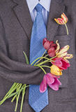 Tweed jacket with  tulips background. The old brown tweed jacket with a bouquet of tulips hangs on a hanger background Royalty Free Stock Photos