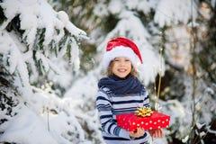 Tweede kerstdag De jongen in Kerstman ` s GLB en een sjaal houdt een heldere doos met een in hand gift Royalty-vrije Stock Afbeelding