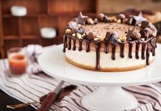 Tweedraads die chocoladekaastaart met suikergoed en het berijpen wordt verfraaid stock foto's