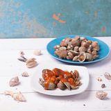Tweekleppig schelpdier met shell op een blauwe plaat op een witte houten achtergrond met Spaanse pepers en tomatensaus Stock Afbeelding