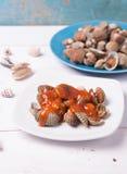 Tweekleppig schelpdier met shell op een blauwe plaat op een witte houten achtergrond met Spaanse pepers en tomatensaus Stock Foto's