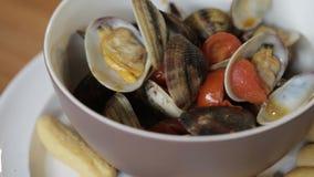 Tweekleppige schelpdieren en tomaten in een kop stock video
