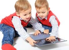 Tweeling broers die voor laptop vechten Stock Afbeeldingen