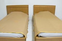 Tweeling bruine bed en deken op witte matras bij ho Stock Afbeelding