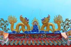 Tweeling gouden Chinese draak op hoogste dak voor buitendecoratie op blauwe hemel, heilige plaats Chinese tempel Royalty-vrije Stock Afbeelding