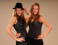 Tweeling meisjes die in zwarte kleren elkaar koesteren Stock Afbeeldingen