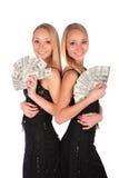 Tweeling meisjes met Dollars Stock Afbeeldingen