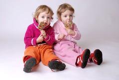 Tweeling meisjes met lollys Stock Fotografie