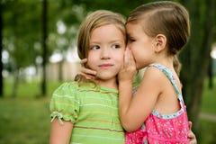 Tweeling twee weinig gefluister van zustermeisjes in oor Royalty-vrije Stock Afbeelding