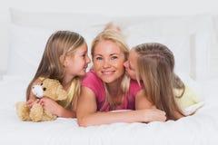 Tweelingen die hun moeder in bed kussen Stock Fotografie