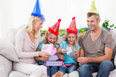 Tweelingen die verjaardagsgift met hun ouders opvouwen Stock Afbeelding