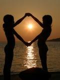 Tweelingen die in zonsondergang spelen Stock Fotografie