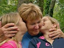 Tweelingen, zusterkus een grootmoeder Royalty-vrije Stock Fotografie