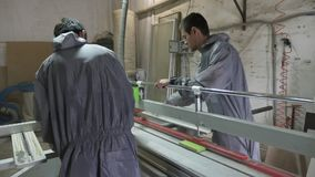 Tweelingenarbeiders die hout in timmermansworkshop snijden met lijst cirkelzaag stock video