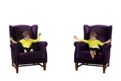 Tweelingjongens die op leunstoelen gelukkige boos zitten Stock Fotografie