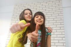 Tweelingzusters die O.k. zeggen stock foto's