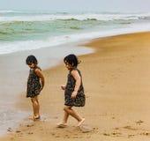 Tweelingzusters Indische jonge geitjes die op puri zandig strand lopen in kust die vreugde uitdrukken royalty-vrije stock afbeeldingen