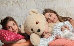 Tweelingzusters met hoofdkussens in de slaapkamer Stock Afbeelding