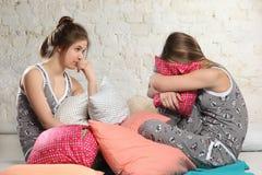 Tweelingzusters met hoofdkussens in de slaapkamer Stock Foto