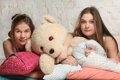 Tweelingzusters met hoofdkussens in de slaapkamer Royalty-vrije Stock Afbeeldingen