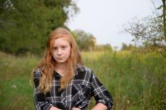 Tween μακρυμάλλες κόκκινο κεφάλι με το πράσινο τοπίο Στοκ Φωτογραφία