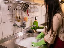 Asian  American girl washing dishes Royalty Free Stock Photography