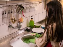 Asian  American girl washing dishes Royalty Free Stock Photos
