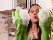 Asian  American girl washing dishes with funny expression Royalty Free Stock Images