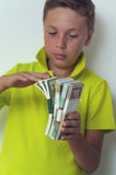 Tween boy counting dollar bills Stock Photo