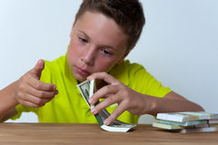 Tween boy counting dollar bills Stock Photos