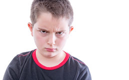 Tween Boy Frowning Disapprovingly at Camera. Head and Shoulders Close Up Portrait of Young Tween Boy Wearing Black and Red T-Shirt Frowning with Furrowed Brow at stock photography