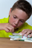 Tween boy sitting with dollar bills heaps on table Stock Image