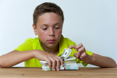 Tween boy sitting at the table with dollar bills. Royalty Free Stock Image
