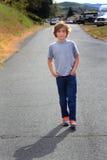 Tween Boy on a Stroll. A cute preteen country boy walking strolling down a neighborhood country road. Shallow depth of field Stock Photo