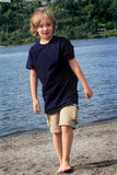 Tween Boy Walking. A preteen country boy walking on a sandy riverbank. Shallow depth of field Stock Image