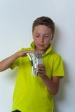 Tween boy wearing t-shirt counting dollar bills Stock Images