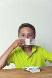 Tween child covering mouth with dollar bills Royalty Free Stock Photography
