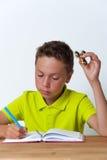 Tween de jongenszitting bij de lijst met friemelt spinner Stock Foto's