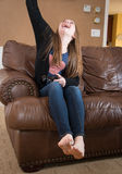 Tween girl celebrating a point scored during a video game. Tween female who is sitting on a brown leather couch.  Her are is raised she is cheering and Stock Photography