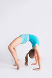 Tween girl in gymanstics bridge pose. Young doing arched back in a high bridge on white backdrop Stock Photo
