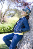 Tween Girl leaning on Tree Stock Photo