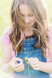 Tween girl with long hair, wishing on a daisy Royalty Free Stock Photos