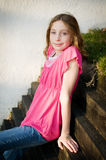 Tween girl outdoors. Blond, blue eyed twelve year old girl sitting outside on a sunny summer day Stock Photography