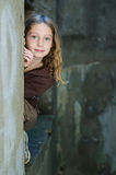 Tween girl peeking around a wall stock photos