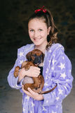 Tween girl in pyjamas with new puppy Stock Photography