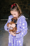 Tween girl in pyjamas with new puppy, kissing Stock Photo