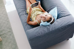 Tween girl relaxing on couch at home. 10 years old tween girl relaxing on a couch, listening to music in headphones and playing with tablet pc. Child chilling on Stock Image