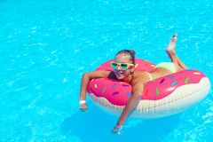 Tween girl in resort pool. Tween girl relaxing on the inflatable ring in resort pool in Thailand Royalty Free Stock Images